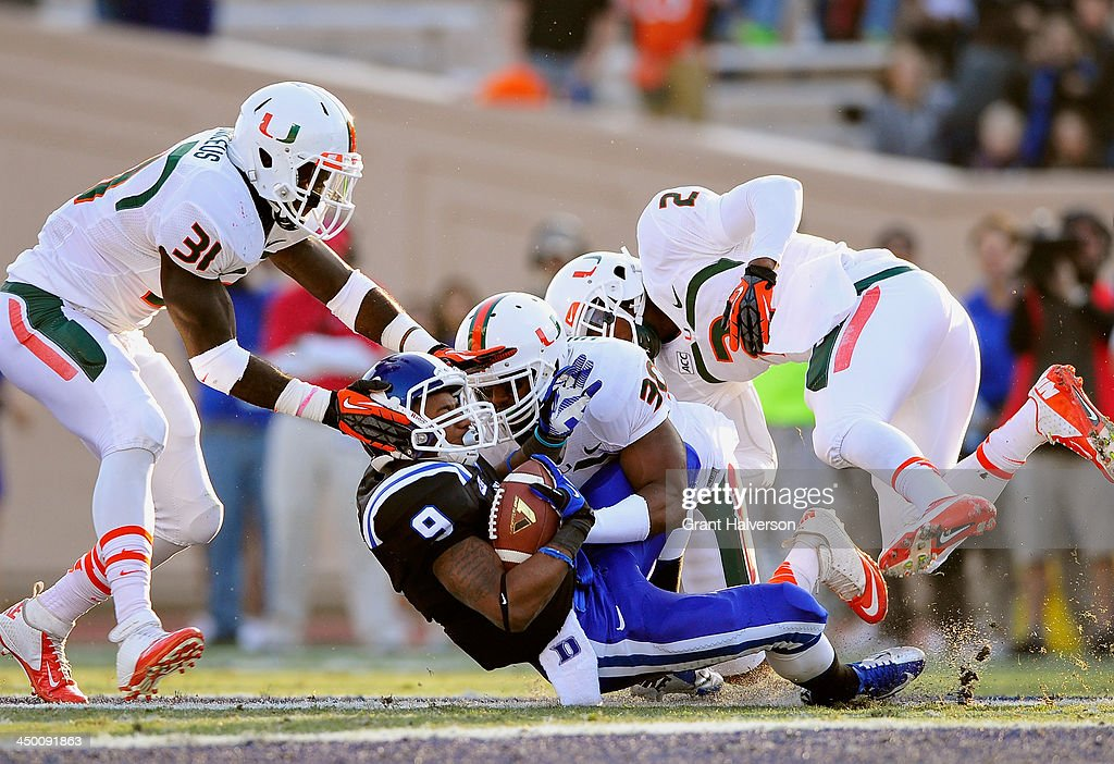 Tyrone Cornelius #31, Al Highsmith #30 and Deon Bush #2 of the Miami Hurricanes tackle Josh Snead #9 of the Duke Blue Devils during play at Wallace Wade Stadium on November 16, 2013 in Durham, North Carolina.