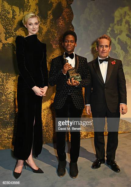 Tyrone Huntley winner of the Emerging Talent Award in partnership with Burberry poses with presenters Elizabeth Debicki and Tom Hollander at the 62nd...
