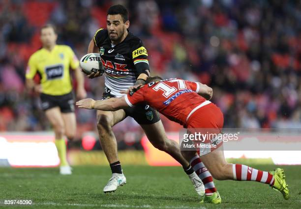 Tyrone May of the Panthers is tackled by Josh McCrone of the Dragons during the round 25 NRL match between the Penrith Panthers and the St George...