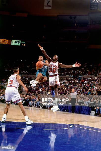 Tyrone 'Mugsy' Bogues of the Charlotte Hornets goes up for a shot against Xavier McDaniel of the New York Knicks during a game circa 1991 at Madison...