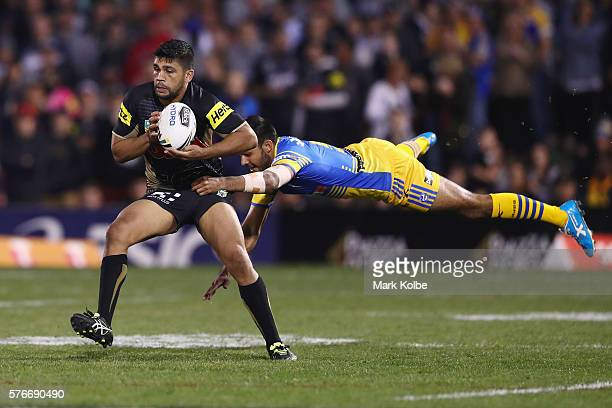 Tyrone Peachey of the Panthers evades the tackle of Bevan French of the Eels during the round 19 NRL match between the Penrith Panthers and the...