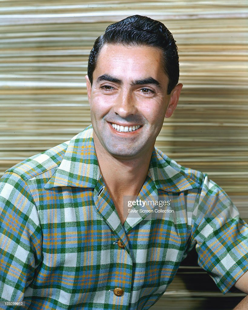 Tyrone Power (1914-1958), US actor, wearing a green-and-white plaid shirt, smiling in a studio portrait, circa 1950.