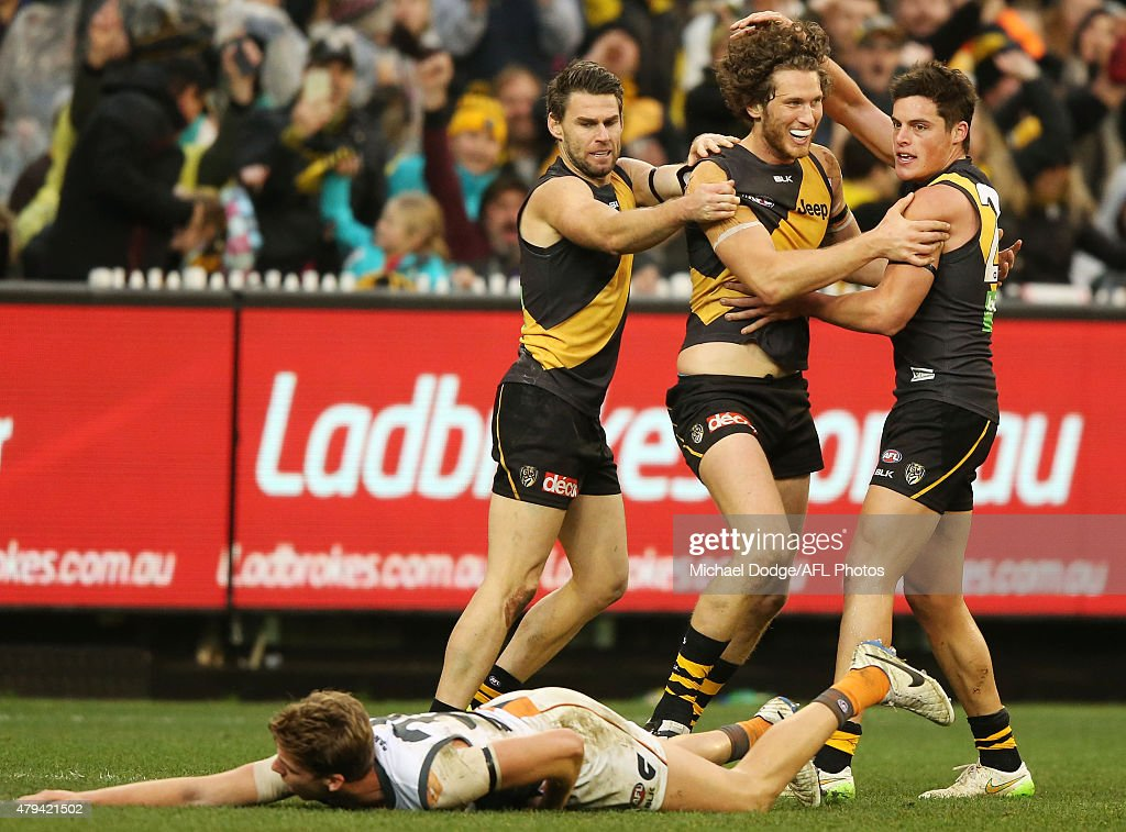 Tyrone Vickery of the tigers celebrates a goal with Chris Newman and Nathan Gordon during the round 14 AFL match between the Richmond Tigers and the...