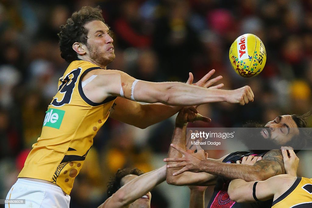 Tyrone Vickery of the Tigers punches the ball away from Courtenay Dempsey of the Bombers during the round 10 AFL match between the Essendon Bombers and the Richmond Tigers at Melbourne Cricket Ground on May 28, 2016 in Melbourne, Australia.