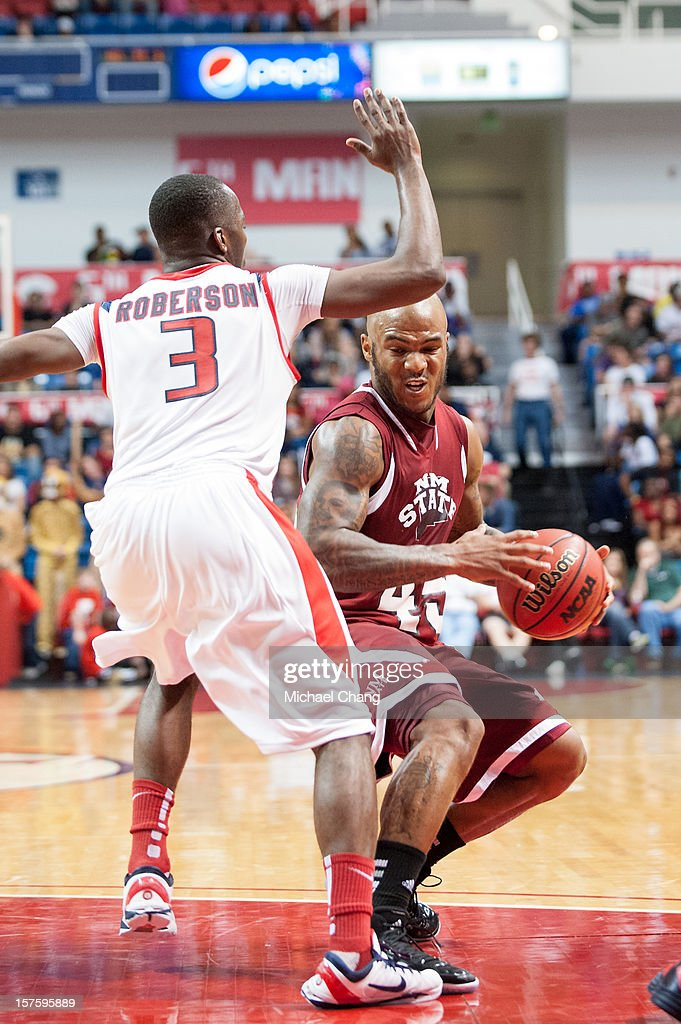 Tyrone Watson #45 of the New Mexico State Aggies attempts to maneuver around Xavier Roberson #3 of the South Alabama Jaguars at USA Mitchell Center on December 4, 2012 in Mobile, Alabama. At halftime New Mexico State leads South Alabama 31-25.