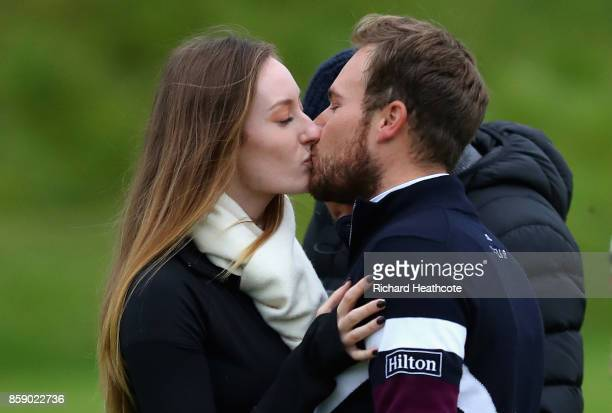 Tyrrell Hatton of England celebrates victory with a kiss from his girlfriend Emily Braisher following the final round of the 2017 Alfred Dunhill...