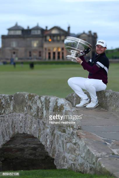Tyrrell Hatton of England celebrates victory with the trophy on the Swilken Bridge following the final round of the 2017 Alfred Dunhill Championship...