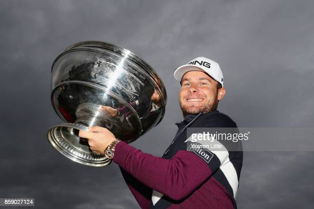 Tyrrell Hatton of England celebrates victory with the trophy following the final round of the 2017 Alfred Dunhill Championship at The Old Course on...