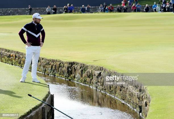 Tyrrell Hatton of England finds his ball in teh Swilcan Burn after his second shot on the first hole during the final round of the 2017 Alfred...