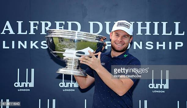 Tyrrell Hatton of England holds the trophy aloft on the 18th green after winning the Alfred Dunhill Links Championship at The Old Course on October 9...