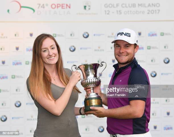 Tyrrell Hatton of England holds the winners trophy with his girlfriend Emily Braisher after the final round of The Italian Open at Golf Club Milano...