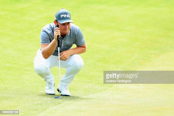 Tyrell Hatton of England lines up a putt on the 16th green during the second round of the 2017 US Open at Erin Hills on June 16 2017 in Hartford...