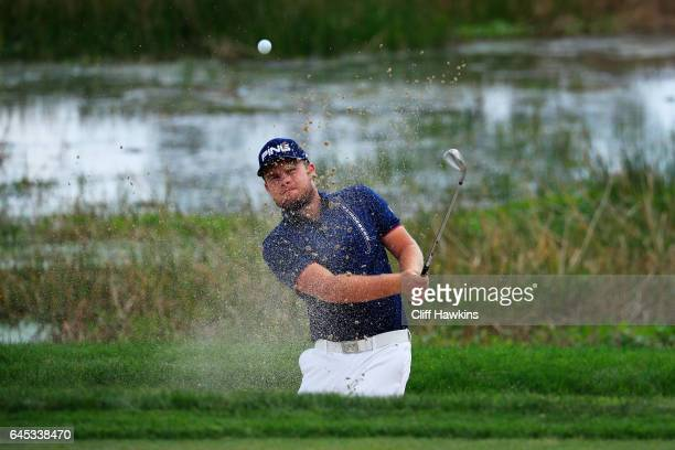 Tyrrell Hatton of England plays a shot from a bunker on the second hole during the third round of The Honda Classic at PGA National Resort and Spa on...