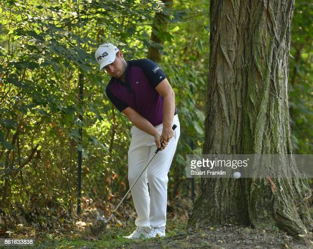 Tyrrell Hatton of England plays a shot on the first hole from by a tree during the final round of The Italian Open at Golf Club Milano Parco Reale di...