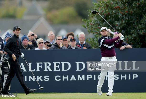 Tyrrell Hatton of England plays his tee shot on the third hole watched by his playing partner Gregory Bourdy of France during the final round of the...