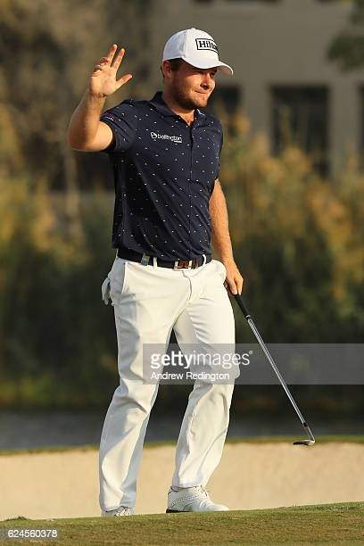 Tyrrell Hatton of England reacts to holing his bunker shot on the 17th hole for par during day four of the DP World Tour Championship at Jumeirah...