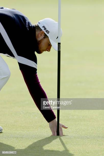 Tyrrell Hatton of England retrieves his ball from the hole after holing his fourth shot on the first hole during the final round of the 2017 Alfred...