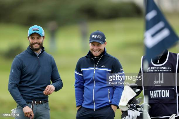Tyrrell Hatton of England with his amateur partner Jamie Dornan after he had holed his second shot on the 16th hole for a birdie during the second...