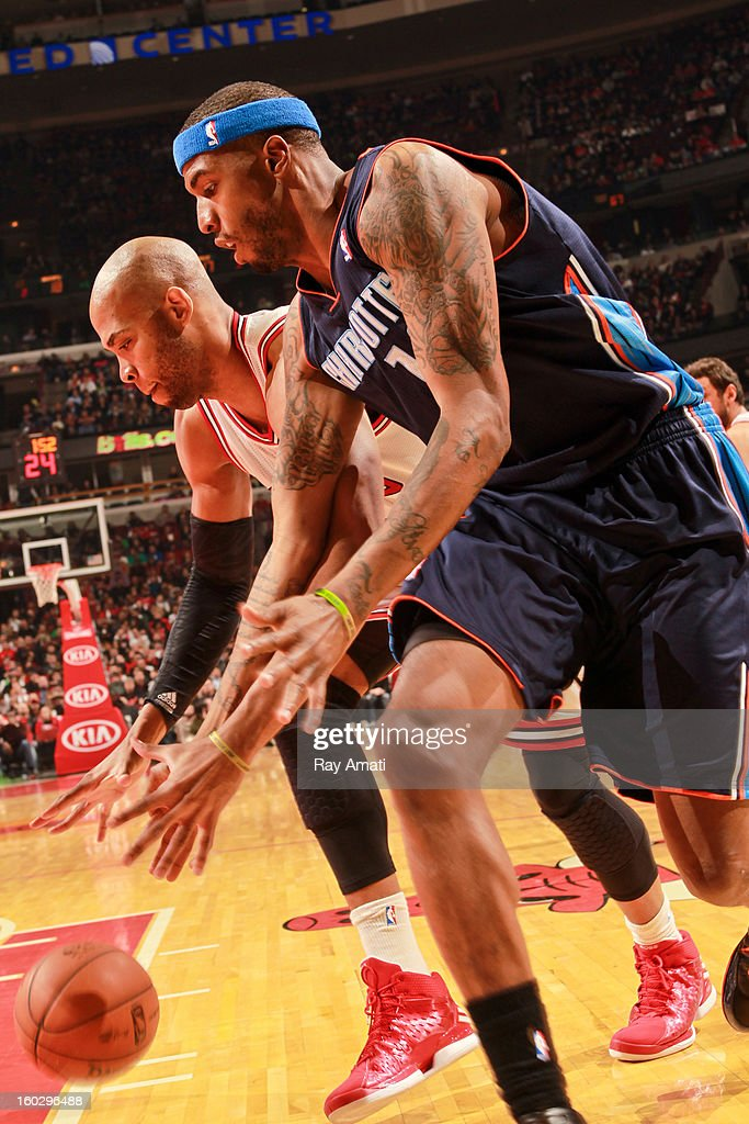 Tyrus Thomas #12 of the Charlotte Bobcats and Taj Gibson #22 of the Chicago Bulls chase after a loose ball during their game on January 28, 2013 at the United Center in Chicago, Illinois.