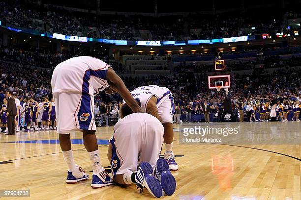 Tyshawn Taylor Marcus Morris and Markieff Morris of the Kansas Jayhawks remain on the floor dejected after they lost 6967 against the Northern Iowa...