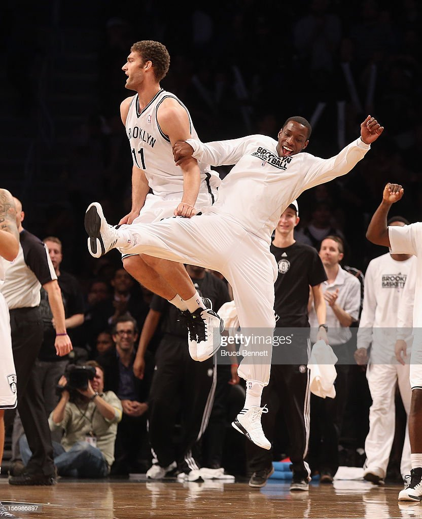 Tyshawn Taylor #41 of the Brooklyn Nets (R) bumps Brook Lopez #11 (L) following Lopez's bucket late in the fourth quarter against the New York Knicks at the Barclays Center on November 26, 2012 in the Brooklyn borough of New York City.