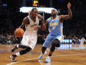 Tyshawn Taylor of the Brooklyn Nets drives against Ty Lawson of the Denver Nuggets during the second half at Barclays Center on December 3 2013 in...