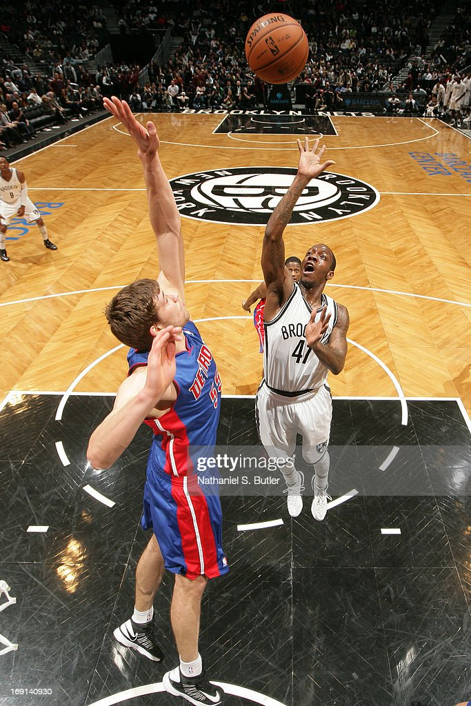 Tyshawn Taylor of the Brooklyn Nets shoots against Viacheslav Kravtsov of the Detroit Pistons on April 17 2013 at the Barclays Center in the Brooklyn...