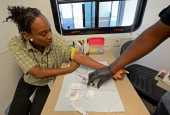Tyshuanna Jackson get her blood drawn for HIV/AIDS and STD testing by Ernest Johnson of John Wesley Community Health Institute in one of their mobile...