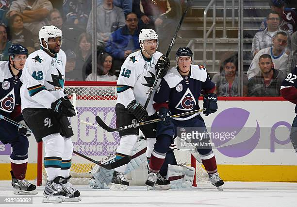 Tyson Barrie of the Colorado Avalanche and Patrick Marleau and Joel Ward of the San Jose Sharks look down ice during the game at the Pepsi Center on...