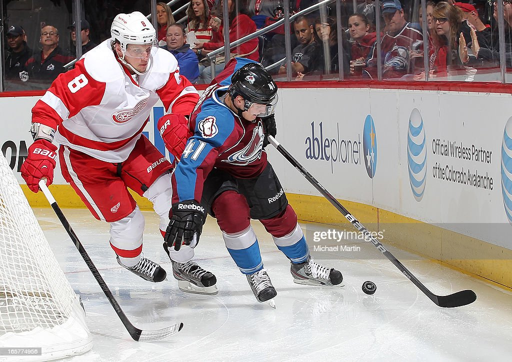 Tyson Barrie #41 of the Colorado Avalanche skates the puck against Justin Abdelkader #8 of the Detroit Red Wings at the Pepsi Center on April 5, 2013 in Denver, Colorado.