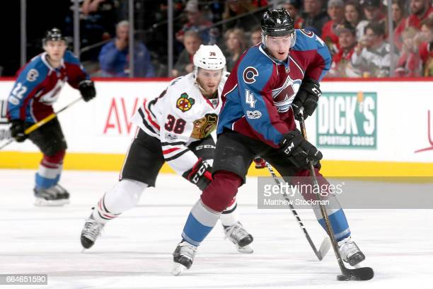 Tyson Barrie of the Colorado Avalanche skates with puck against Ryan Hartman of the Chicago Blackhawks at the Pepsi Center on April 4 2017 in Denver...