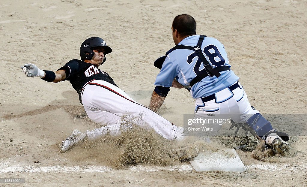 Tyson Byrne of New Zealand slides to base as Bruno Montroni of Argentina attempts the tag during the pool B match between New Zealand and Argentina at Tradstaff Sports Stadium on March 5, 2013 in Auckland, New Zealand.