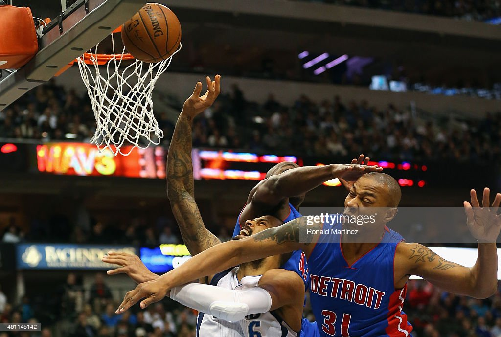 Tyson Chandler of the Dallas Mavericks is fouled by Anthony Tolliver of the Detroit Pistons while also defended by Caron Butler at American Airlines...