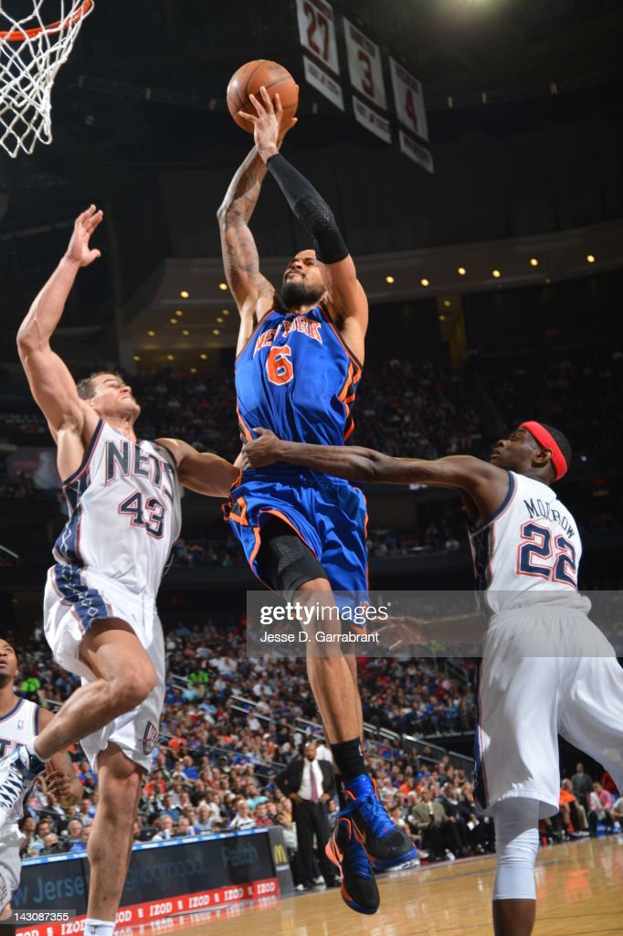 <a gi-track='captionPersonalityLinkClicked' href=/galleries/search?phrase=Tyson+Chandler&family=editorial&specificpeople=202061 ng-click='$event.stopPropagation()'>Tyson Chandler</a> #6 of the New York Knicks dunks over <a gi-track='captionPersonalityLinkClicked' href=/galleries/search?phrase=Kris+Humphries&family=editorial&specificpeople=209199 ng-click='$event.stopPropagation()'>Kris Humphries</a> #43 and <a gi-track='captionPersonalityLinkClicked' href=/galleries/search?phrase=Anthony+Morrow&family=editorial&specificpeople=814354 ng-click='$event.stopPropagation()'>Anthony Morrow</a> #22 of the New Jersey Nets on April 18, 2012 at the Prudential Center in Newark, New Jersey.