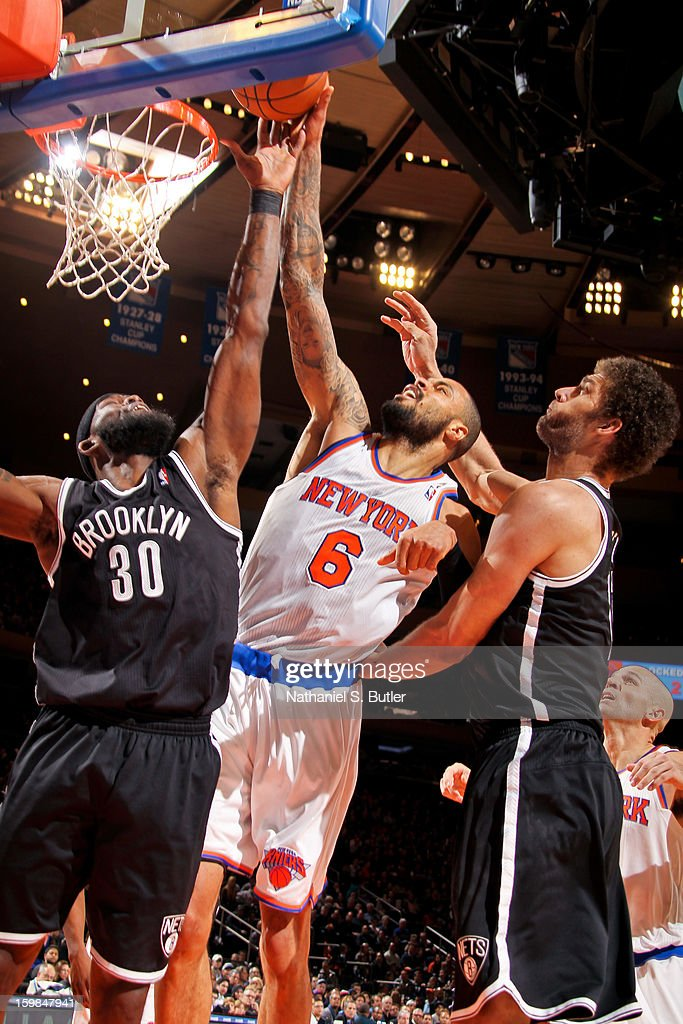 Tyson Chandler #6 of the New York Knicks fights for a rebound against Reggie Evans #30 and Brook Lopez #11 of the Brooklyn Nets on January 21, 2013 at Madison Square Garden in New York City.