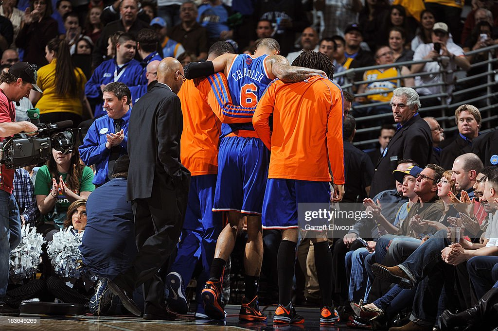Tyson Chandler #6 of the New York Knicks is helped off the court after bruising his knee during play against the Denver Nuggets on March 13, 2013 at the Pepsi Center in Denver, Colorado.
