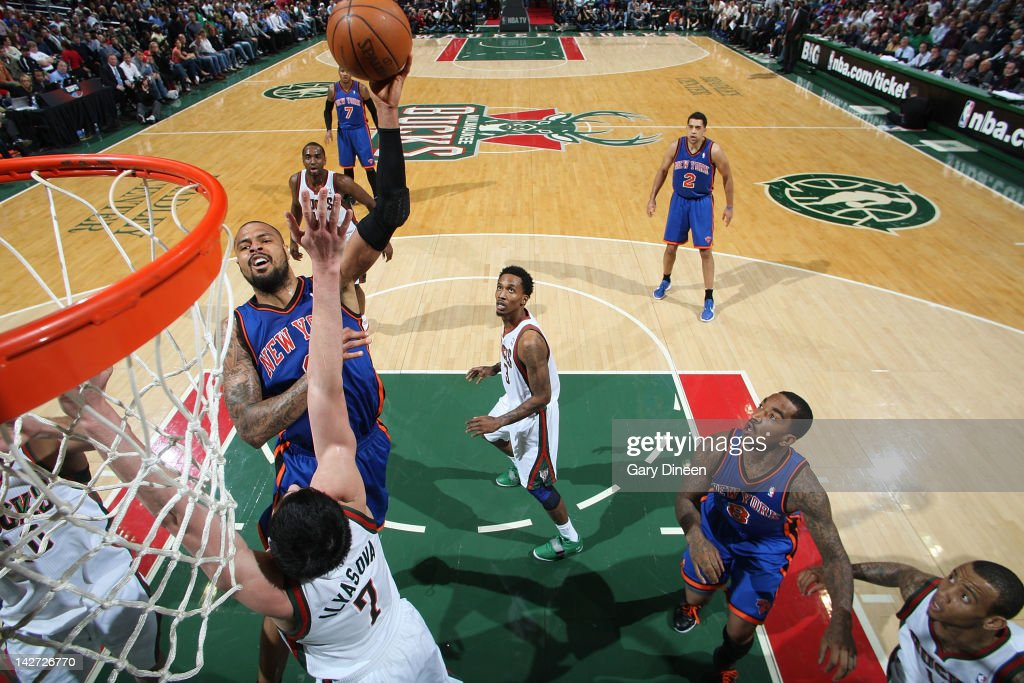 <a gi-track='captionPersonalityLinkClicked' href=/galleries/search?phrase=Tyson+Chandler&family=editorial&specificpeople=202061 ng-click='$event.stopPropagation()'>Tyson Chandler</a> #6 of the New York Knicks shoots against <a gi-track='captionPersonalityLinkClicked' href=/galleries/search?phrase=Ersan+Ilyasova&family=editorial&specificpeople=557070 ng-click='$event.stopPropagation()'>Ersan Ilyasova</a> #7 of the Milwaukee Bucks on April 11, 2012 at the Bradley Center in Milwaukee, Wisconsin.