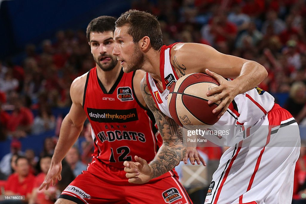 Tyson Demos of the Hawks looks to drive past Kevin Lisch of the Wildcats during game one of the NBL Semi Final Series between the Perth Wildcats and the Wollongong Hawks at Perth Arena on March 28, 2013 in Perth, Australia.