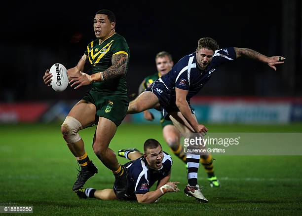 Tyson Frizell of Australia powers past Ben Hellewell and Euan Aitken of Scotland during the Four Nations match between the Australian Kangaroos and...