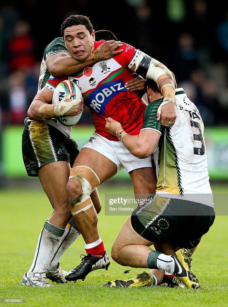 Tyson Frizell of Wales is tackled by Dominque Peyroux (L) and Brad Takairangi (R) of the Cook Islands during the Rugby World Cup Group D match between Wales and the Cook Islands at The Gnoll on November 10, 2013 in Neath, Wales.