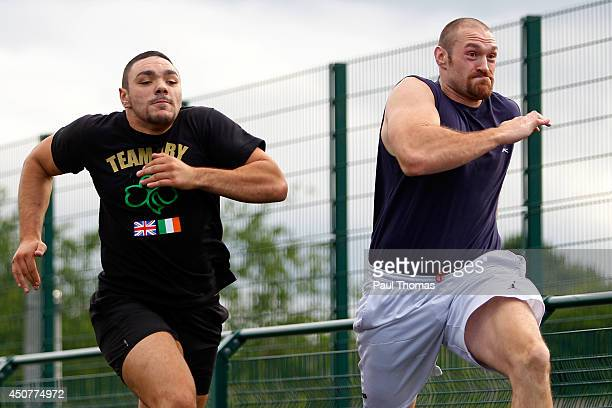 Tyson Fury and Young Fury run during the Tyson Fury Media Session at the Eddie Davies Football Academy on June 17 2014 in Bolton England