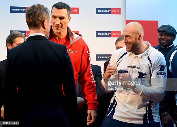 Tyson Fury of UK jokes next to Wladimir Klitschko of Ukraine during the weigh in at Karstadt Sport on November 27 2015 in Essen Germany