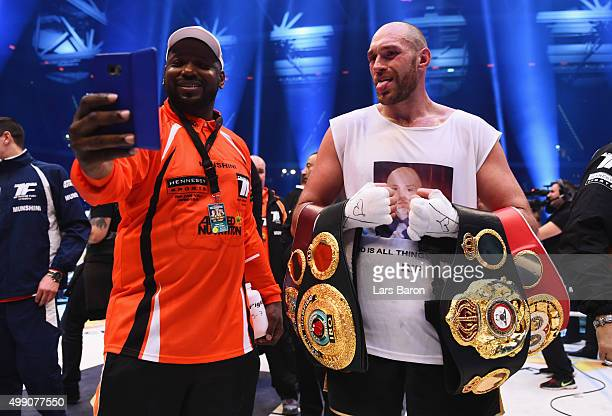 Tyson Fury poses for a photo with belts and team member Clifton Mitchell as he defeats Wladimir Klitschko to become new World Heavyweight Champion...