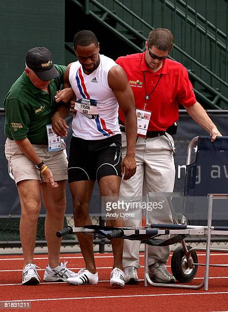 Tyson Gay is helped off the track by medical staff after falling to the track in pain at the back turn of the men's 200 meter quarterfinals during...