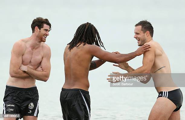Tyson Goldsack Harry O'Brien and Nathan Brown of the Magpies wade in the water during a Collingwood Magpies AFL recovery session at St Kilda Sea...