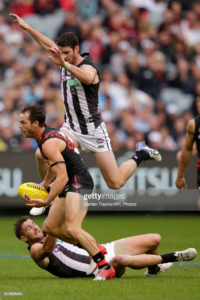 Tyson Goldsack of the Magpies jumps over team mate Jeremy Howe to chase Travis Colyer of the Bombers during the round five AFL match between the Essendon Bombers and the Collingwood Magpies at Melbourne Cricket Ground on April 25, 2017 in Melbourne, Australia.