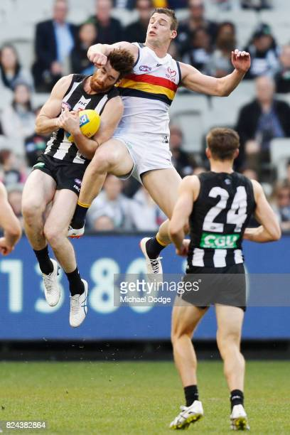Tyson Goldsack of the Magpies marks the ball against Josh Jenkins of the Crows during the round 19 AFL match between the Collingwood Magpies and the...