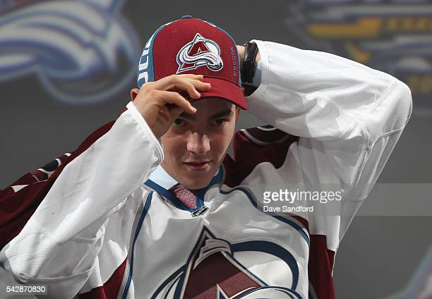 Tyson Jost puts on his hat onstage after being selected tenth overall by the Colorado Avalanche during round one of the 2016 NHL Draft at First...