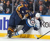Tyson Strachan of the Buffalo Sabres checks Jacob Trouba of the Winnipeg Jets on November 26 2014 at the First Niagara Center in Buffalo New York