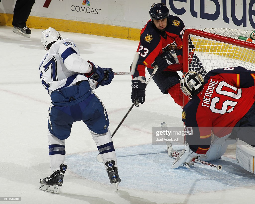 Tyson Strachan #23 of the Florida Panthers watches as <a gi-track='captionPersonalityLinkClicked' href=/galleries/search?phrase=Benoit+Pouliot&family=editorial&specificpeople=879830 ng-click='$event.stopPropagation()'>Benoit Pouliot</a> #67 of the Tampa Bay Lightning scores the game-winning goal past Goaltender <a gi-track='captionPersonalityLinkClicked' href=/galleries/search?phrase=Jose+Theodore&family=editorial&specificpeople=202011 ng-click='$event.stopPropagation()'>Jose Theodore</a> #60 at the BB&T Center on February 16, 2013 in Sunrise, Florida. The Lightning defeated the Panthers 6-5 in overtime.